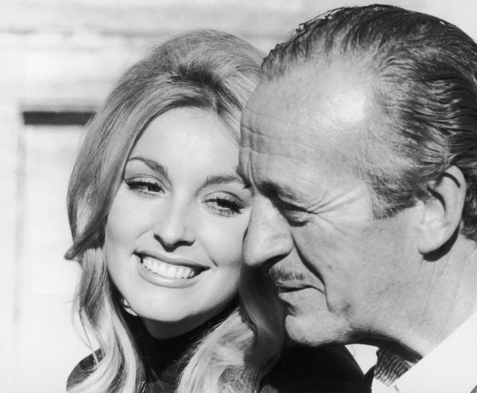 Sharon Tate beams as she poses with her friend, actor David Niven.